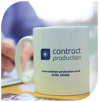 A close up of a drinks mug, branded with the Contract Production logo