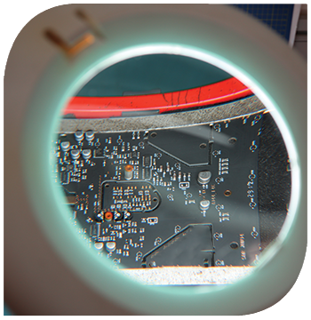 A close up of a prototype printed circuit board viewed through a magnification lense